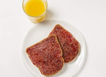 Glass of fresh orange juice and 2 thick slices of wholemeal toast with jam