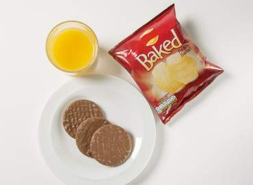 Glass of fresh orange juice with a packet of crisps and chocolate digestives