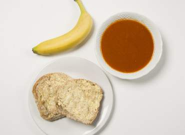 Homemade tomato soup and a wholemeal bread roll with lower fat spread, followed by a banana
