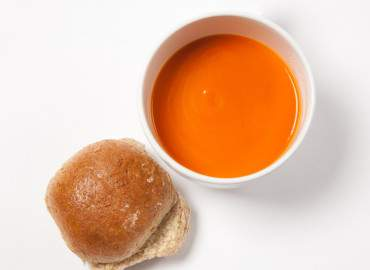 Bowl of tinned tomato soup and a bread roll with lower fat spread