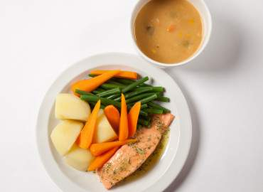 Bowl of tinned lentil soup, and salmon with potatoes and vegetables