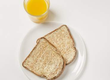 Glass of fresh orange juice with 2 slices of wholemeal toast with lower fat spread