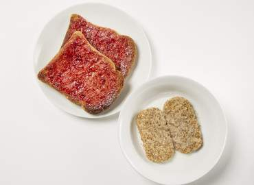 Bowl of wheat bisks and two slices of wholemeal toast with jam