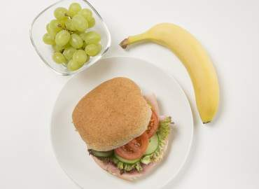 Ham salad on a wholemeal roll followed by a handful of grapes and a banana