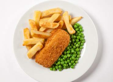 Oven baked haddock with oven chips and vegetables