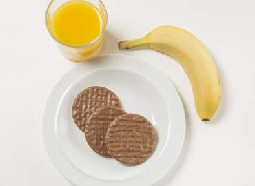 Glass of fresh orange juice with chocolate digestives and a banana