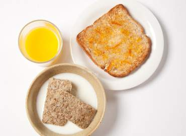 Bowl of wheat bisks, slice of wholemeal toast and marmalade, and a glass of fresh orange juice