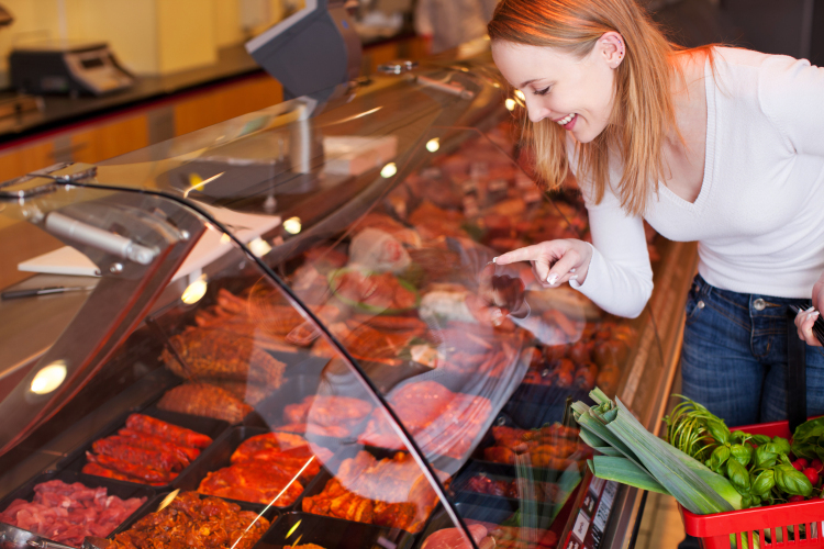 Woman in butchers looking at and pointing to different types of meat on display