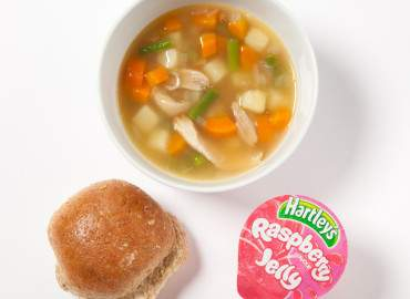 Homemade chicken and vegetable soup, a bread roll with lower fat spread, and a jelly pot
