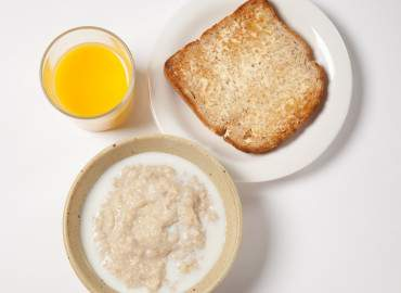 Bowl of porridge, slice of wholemeal toast and lower fat spread, and a glass of fresh orange juice
