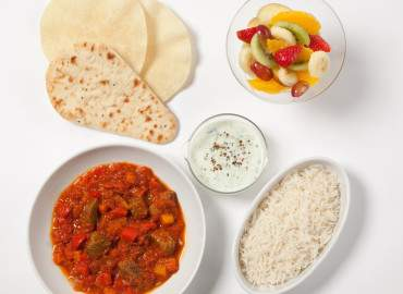 Beef curry with brown rice, raita, naan bread and poppadoms, followed by a fruit salad