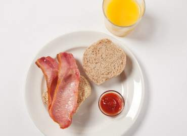 Bacon roll with tomato ketchup and a glass of fresh orange juice