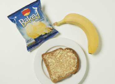 Packet of crisps, banana, and slice of toast with lower fat spread