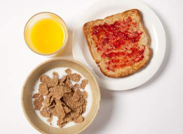 Bowl of wholegrain breakfast flakes, slice of wholemeal toast and jam, and glass of fresh orange juice