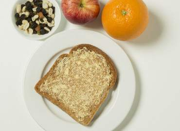 Apple, orange, raisins and slice of toast with lower fat spread