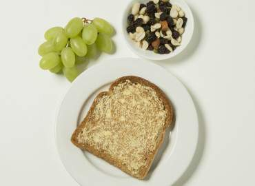 Mixed nuts, raisins, and grapes, slice of toast with lower fat spread